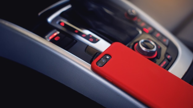 Smartphone in red case on the modern car interior
