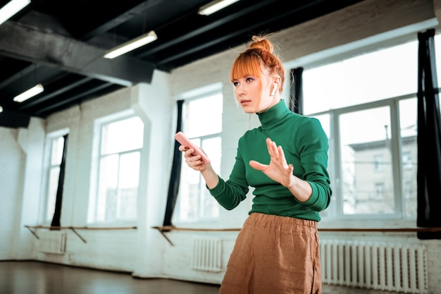 Смартфон. рыжий профессиональный инструктор по йоге в зеленой водолазке держит телефон в руке