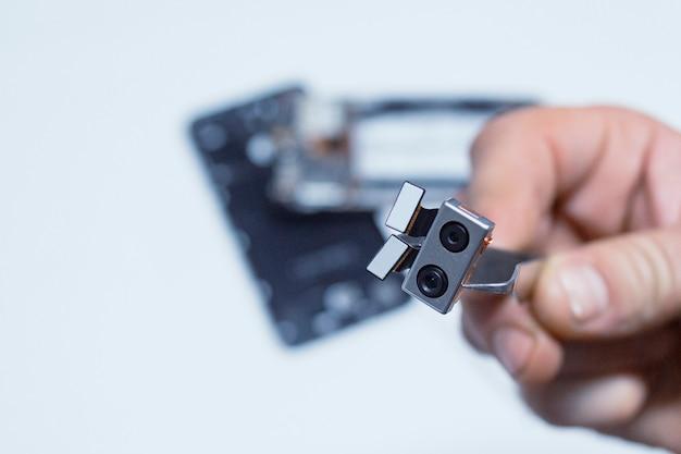 スマートフォンの修理。電話の修理担当者は、組み立てられていない携帯電話を背景に、カメラを手にピンセットを持っています。