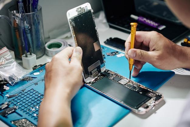 Smartphone repairman removing screws