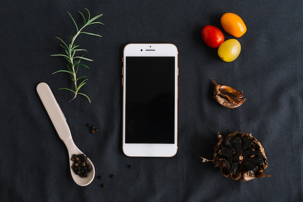 Smartphone; rosemary; cherry tomatoes; black pepper and garlic on dark background