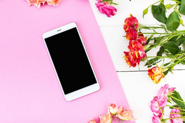 Smartphone, roses on the table