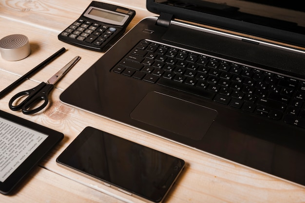 Smartphone; scissor; calculator; pen; laptop and ebook reader on wooden desk