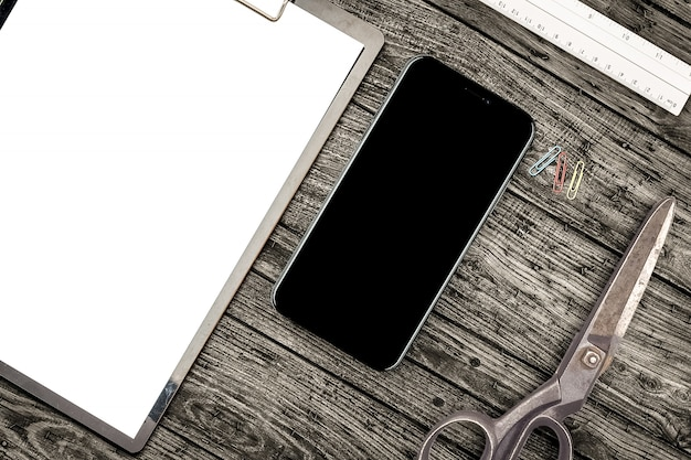 Smartphone, scissors and clipboard on desk