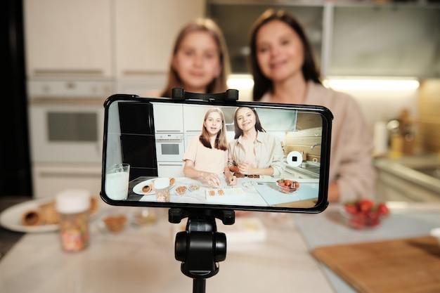 Экран смартфона во время прямой трансляции мастер-класса по домашней кулинарии, где две молодые женщины готовят домашнее мороженое на кухне