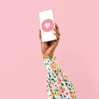 ソーシャルメディアのハートのアイコンとスマートフォンの画面の手
