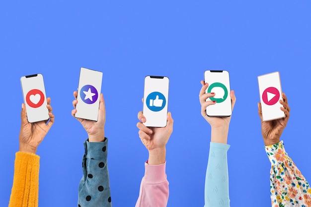 ソーシャルメディアのアイコンとスマートフォンの画面の手