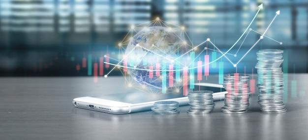 コインの山の成長とチャートの肯定的な指標の横にあるスマートフォンの画面