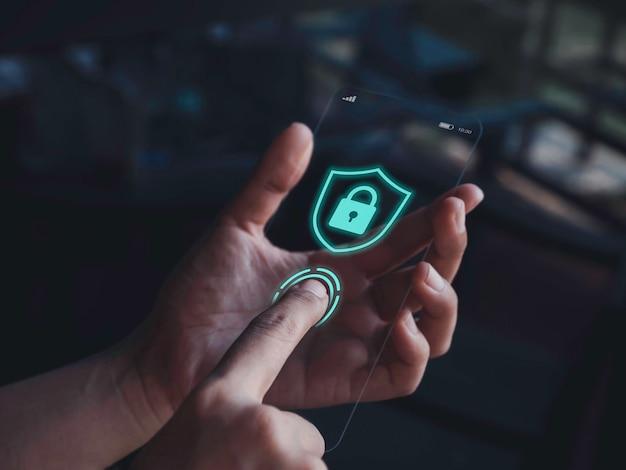 스마트폰 보안 및 개인 정보 보호 개념입니다. 지문 스캐너의 손가락 스캔과 어두운 색조의 배경에 매우 얇은 미래형 유리 전화기 화면에 잠금 아이콘 그래픽이 있는 파란색 방패.