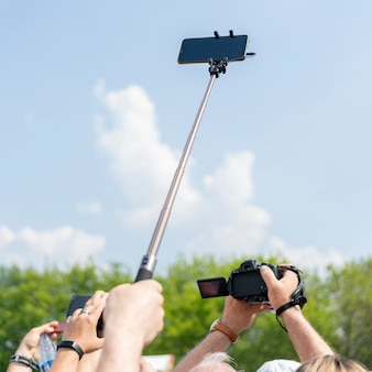 Smartphone on a selfie stick in male hand against the sky.