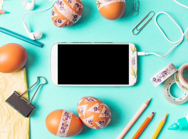 Smartphone between set of brown chicken eggs and stationery