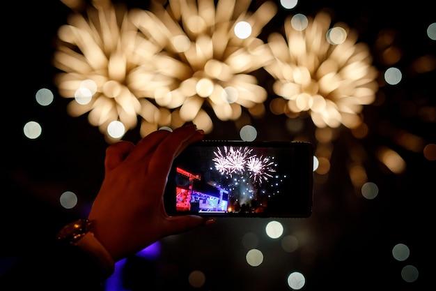 Смартфон стреляет салютом на праздничном мероприятии.