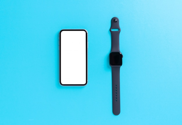 Smartphone and smart watch on light blue wall
