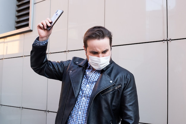 Человек хочет сломать его smartphone, бизнесмена нося защитную маску используя smartphone, концепцию здравоохранения. коронавирус карантин.