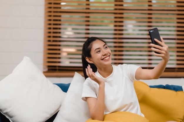 Молодая азиатская женщина подростка используя smartphone видеоконференцию smartphone