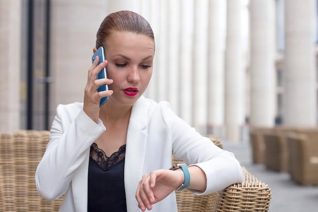 Занятая удивленная бизнес-леди говоря на smartphone и смотря на smartwatch. уверен женщина в куртке вызова, разговор по мобильному телефону, назначение, проверка времени на наручные часы.