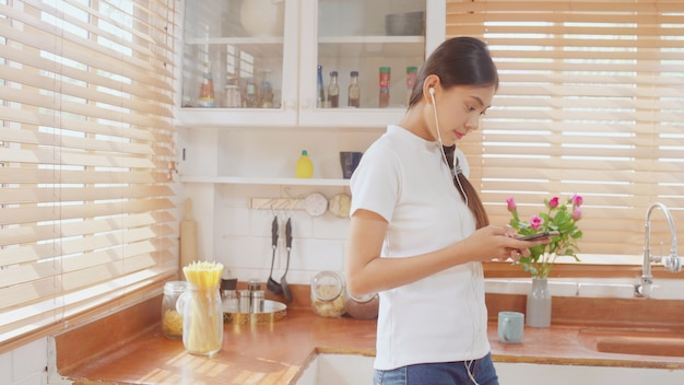 Молодая азиатская женщина подростка выпивая теплый кофе используя музыку smartphone слушая и проверяя social