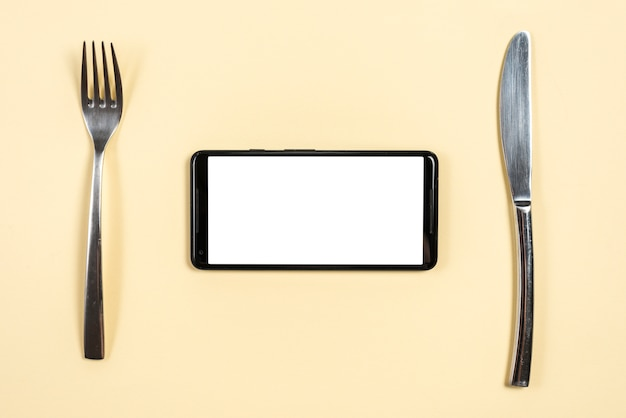 Smartphone between the stainless steel fork and butterknife on beige background