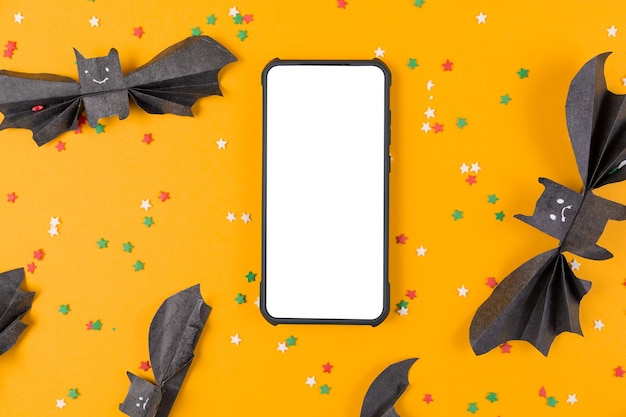 Smartphone surrounded by bats made of paper on orange. flat lay