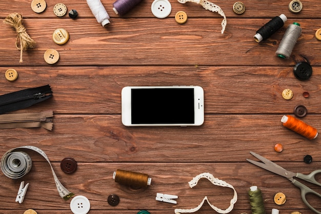 Smartphone surrounded by various sewing accessories on wooden surface
