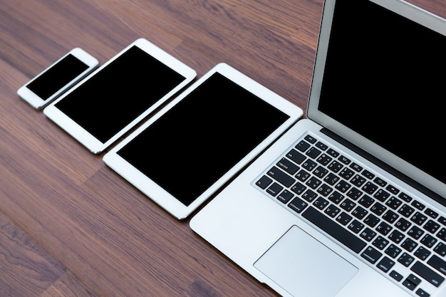 Smartphone, tablets and laptop on a wooden table