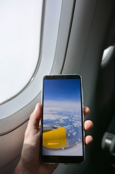 Smartphone taking pictures from the window of the plane