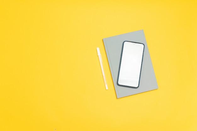 空の画面とcopyspace、平面図、フラットレイアウトと黄色の背景に灰色のノートブックのスマートフォンテンプレート