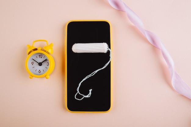 Смартфон для отслеживания менструального цикла и отметок. пмс и концепция критических дней. ватный тампон и желтый сигнал тревоги на розовом фоне.