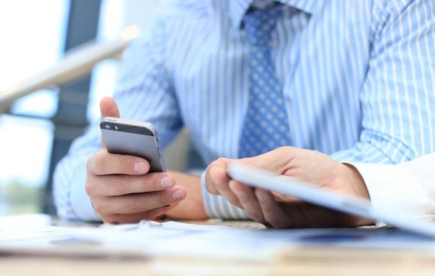 Смартфон, портативный тачпад крупным планом, коллеги, работающие в фоновом режиме.