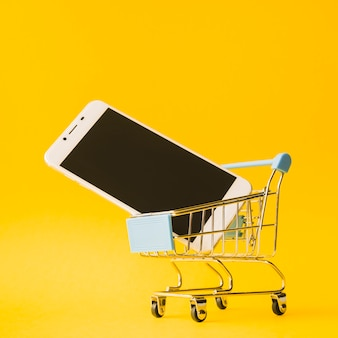 Smartphone in toy supermarket cart