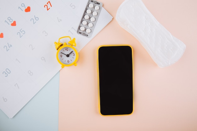 Smartphone to track your menstrual cycle and for marks. pms and the critical days concept. cotton tampon, daily pad and yellow alarm on the pink background.