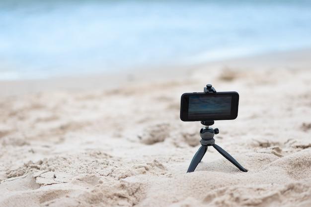 Smartphone on tripod on sand and sea background