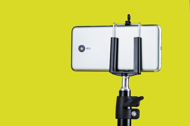 Smartphone on a tripod on a yellow surface for blogging
