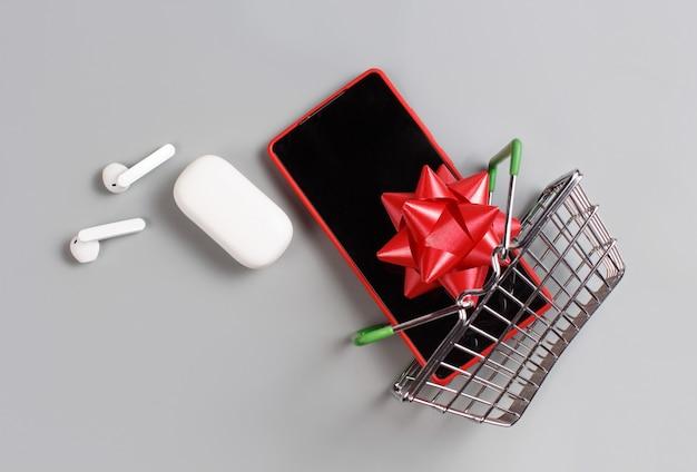 스마트 폰, 흰색 무선 이어폰 및 회색 배경에 장난감 쇼핑 카트 평면도에서 비행하는 활
