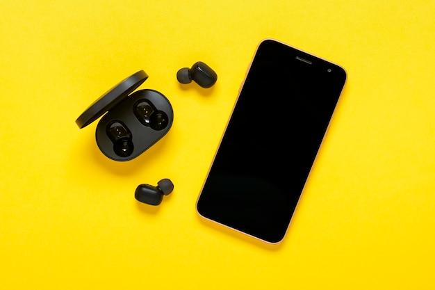 Смартфон, беспроводной наушник на желтом фоне вид сверху