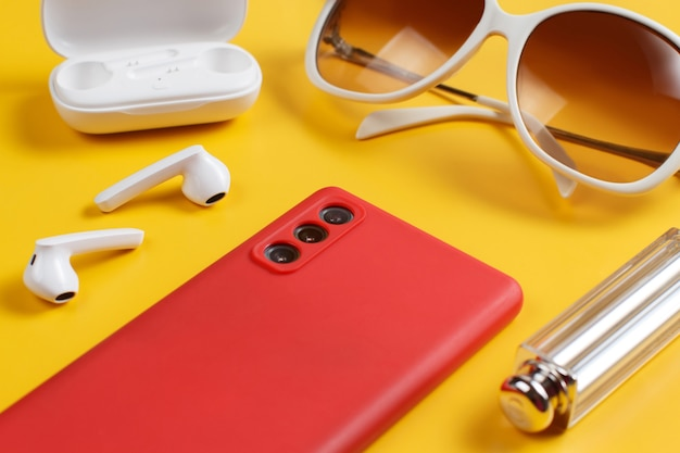 Smartphone, wireless earphones, sunglasses and lipstick on yellow background close up