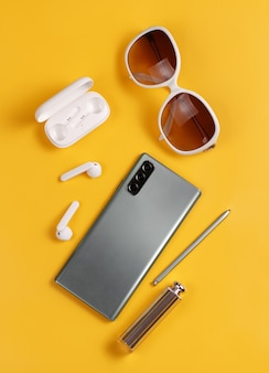 Smartphone, wireless earphones, sunglasses and lipstick on yellow background top view