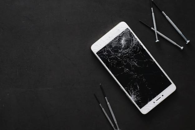 壊れたタッチスクリーンを備えたスマートフォン。携帯電話が壊れています。電話がクラッシュしました。携帯電話の割れたガラスの交換。スマートフォンの修理。