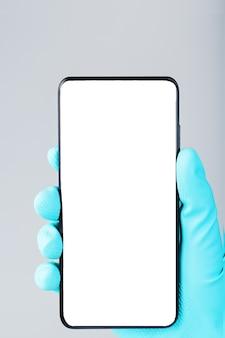 파란색 의료 장갑 클로즈업에서 손에 깨끗한 흰색 화면이있는 스마트 폰