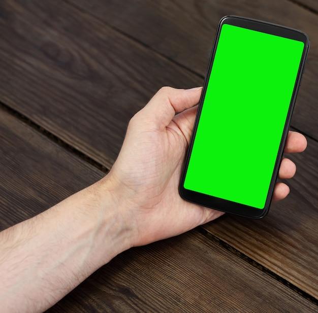 세라믹 커피 컵이 있는 나무 테이블에 녹색 화면이 있는 스마트폰, 수직 위치.
