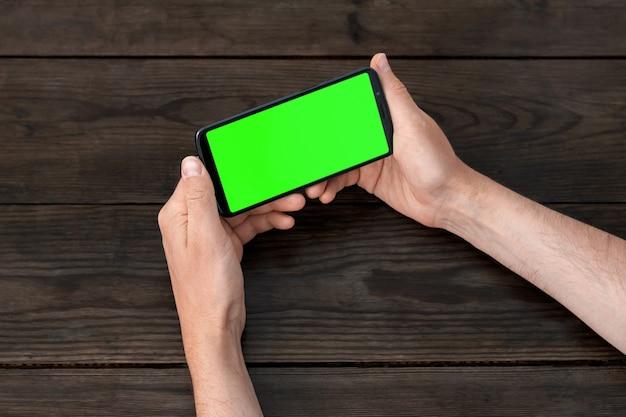 나무 테이블에 손에 녹색 화면이 있는 스마트폰, 수평 위치.