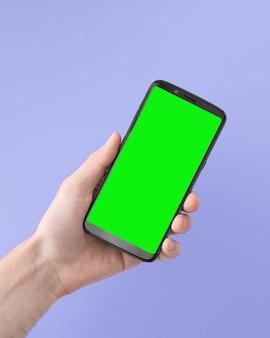 라일락 배경에 오른손에 녹색 화면이 있는 스마트폰, 각진 위치.