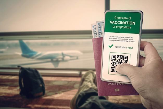앱에 qr 코드가 있는 스마트폰으로 백신 접종 또는 covid-19에 대한 음성 테스트를 확인합니다. 남자는 비행기와 수하물 배낭을 배경으로 공항에서 여권과 스마트폰을 들고 있다