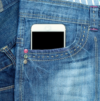 Smartphone with a blank black screen is in the front pocket of blue jeans