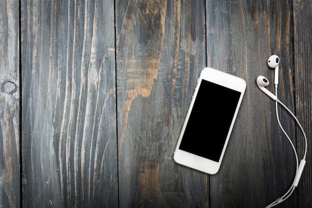 Смартфон с пустым экраном и наушниками на фоне