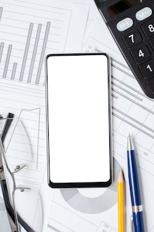 Smartphone with a blank screen on the background of graphs and charts. copy space. the concept of online investing or business or stock trading.