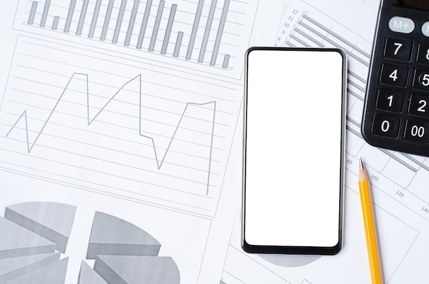 Smartphone with a blank screen on the background of graphs and charts with calculator and pencil