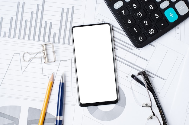 Smartphone with a blank screen on the background of graphs and charts