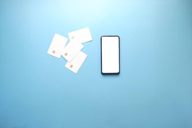 空白の画面、青いテーブルの上のクレジットカードとスマートフォン