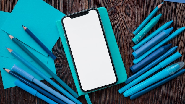 Smartphone with blank screen on diary near blue painting colors and paper over wooden table